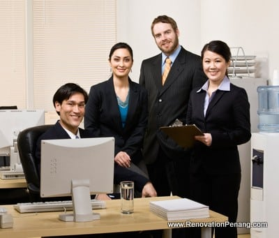 Confident co-workers gathered at desk in office
